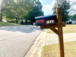 New black mailbox with red flag, wooden stained post, and white house stickers. Neighborhood street in background with green trees and blue sky.