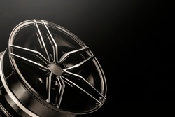 New black shiny alloy wheels rim. light from above, copyspace.