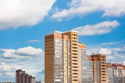 New block of modern apartments with balconies and blue sky with white fluffy clouds in the background