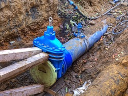 New blue butterfly valve on 300mm underground water pipe. Steel and PE pipeline in excavation under the road