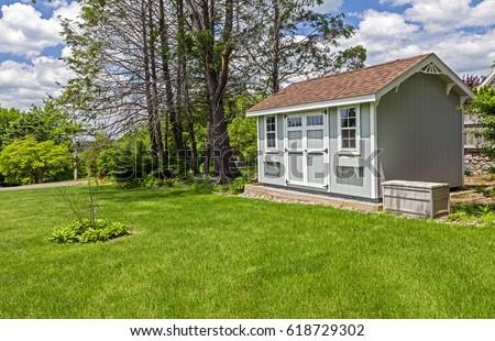 New blue garden shed in beautiful garden