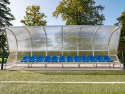 New blue plastic seats on outdoor stadium players bench chairs with new paint below transparent plastic roof.