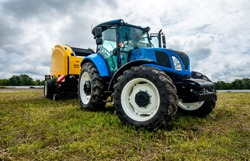 new blue tractor with Baler Roll belt in motion at demonstration field site at agro exhibition.