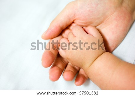 New-born asian baby hand in father\'s palm.