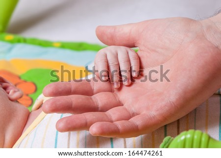 New born baby hand held by father