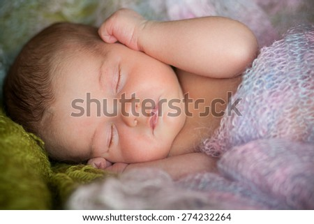 new born baby is lying in shawl, sleeping baby, eyes are closed, on blanket