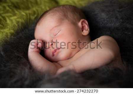new born baby is sleeping in downy shawl, lying baby, eyes are closed, put out tongue