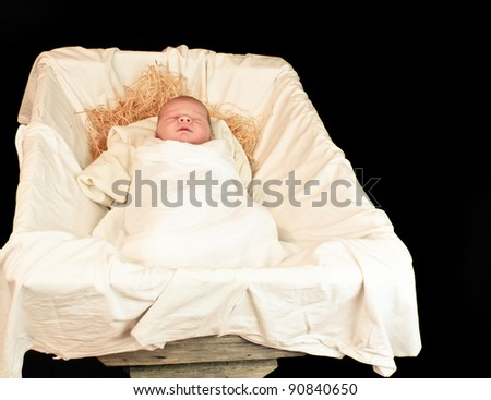 New Born Baby Jesus in a Manger: A Nativity Scene with a Real Child Isolated Over Black