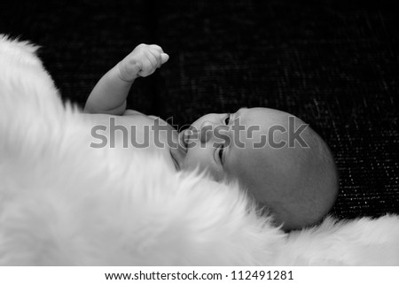 New born baby lying and covered by white fur in black and white