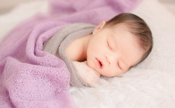 New born baby lying on a soft blanket. Cute  new born baby in natural motion.