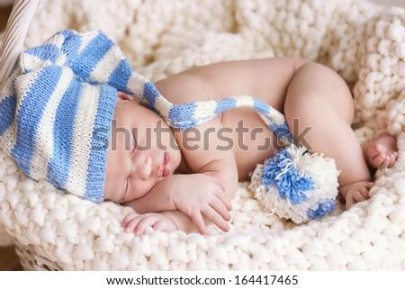 New born baby portrait, lying with hat on head, sleeping