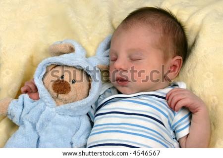 New born baby sleeping with toy stuffed animal