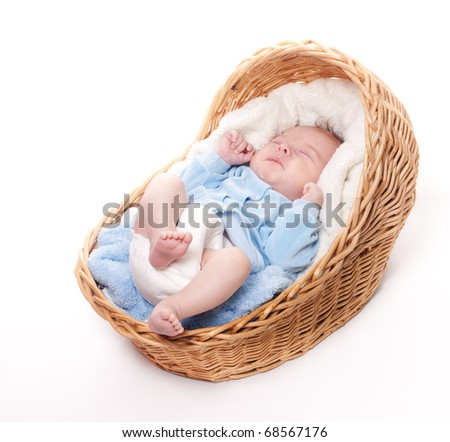 New born baby sleeps in basket with towel on white