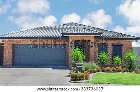 new brick house with green lawn and plants