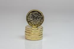 New British one pound coins up close macro studio shot against a shiny reflective White background
