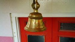 New bronze bell in indian temple isolated on blur background. Close-up of Hindu temple brass bell hanging in gold color