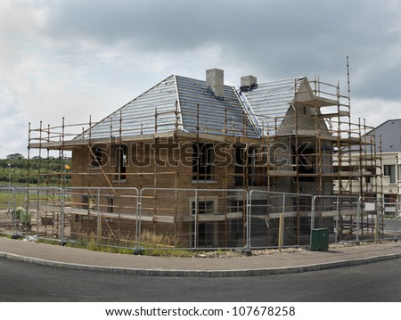 new build home surrounded by fencing and scaffolding