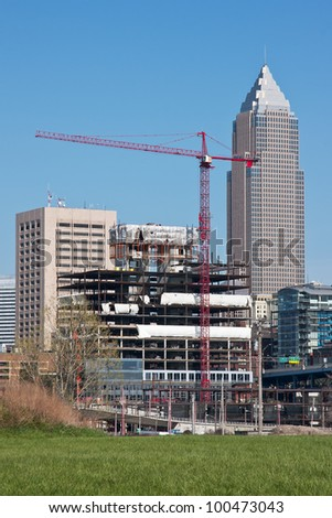 New building construction site with a skyscraper in the background and a cloudless blue sky overhead