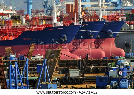 New building tankers in shipyard with cranes on background