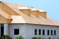 New building under construction showing plywood roof sheeting and three dormers