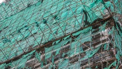 New building under construction with scaffolding and safety nets