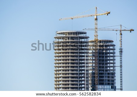 New buildings being constructed. Industrial building site. Shot of two lifting cranes and skyscrapers under construction on clear blue sky background. High-rise buildings and workers. Twin towers. stock photo