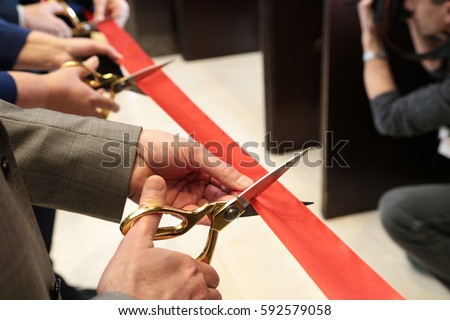 New business venture;  Opening ceremonial red ribbon cutting scissors in hands. Group of people.