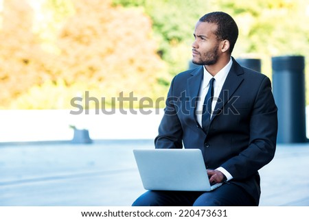 New businesses. African man businessman holding a laptop on his knees and looking away while sitting outside in the formal wear.