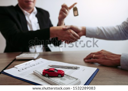 New car buyers and car salesmen are shaking hands to make agreements about car sales. #1532289083