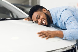 New Car Owner. Happy African American Man Touching Hugging His Brand-New Auto Cherfully Buying Vehicle In Auto Dealership. Selective Focus