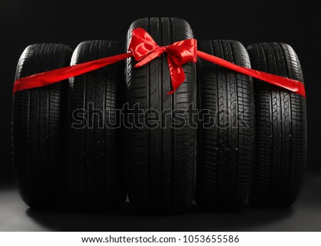 New car tires tied with ribbon on black background