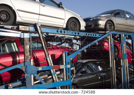 New cars loaded onto Semi Truck transporter ramps.