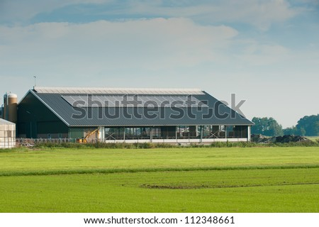 new cattle barn with solar panels on the roof - stock photo