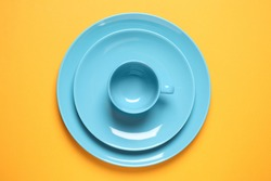 New ceramic dishware on yellow background, top view