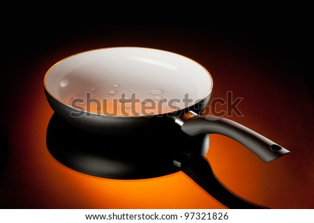 new ceramic frying pan over orange background
