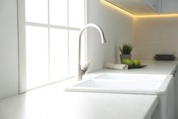 New ceramic sink and modern tap in stylish kitchen interior