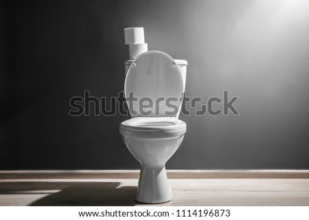 New ceramic toilet bowl near grey wall, side light #1114196873