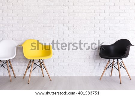 New chairs in white, yellow and black standing in white room with brick wall