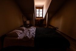New clean European double queen bed with slanted ceiling and window in loft with table and pillows in dark bedroom home apartment room