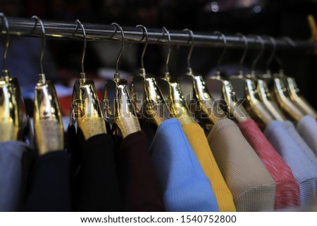 New clothes collection on the golden hangers in the store #1540752800