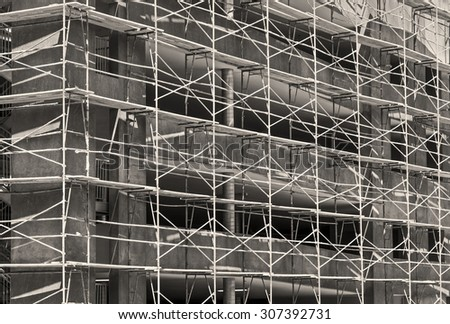 New commercial building construction site scaffolding. Urban development theme. Black and white photo.