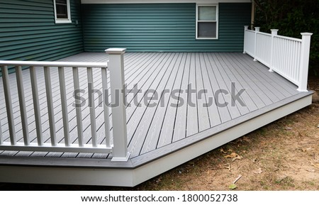New composite deck on the back of a house with green vinyl siding.with whie railings. Stock foto ©