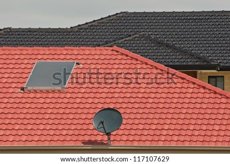 New constructed houses with black satellite dish, water heater panel and tiles pattern as background - stock photo