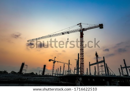 New construction site with crane and mechanical equipments on sunset background.