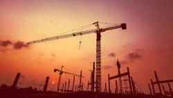 New construction site with cranes on orange sunset, sunrise sky background. Steel frame structure, structural steel beam build large buildings at construction site . construction machinery.