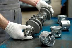 New crankshaft close-up. A set of engine pistons on the car mechanic's desktop. Quality control of spare parts. Car engine repair.