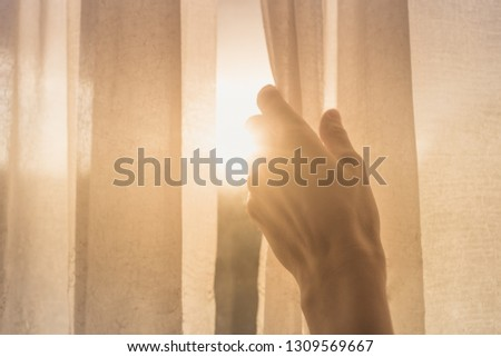 New day concept. Woman's hand opening window curtains early morning with natural light shining through.