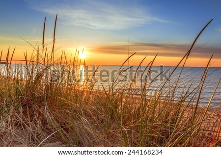 New Day Dawns. The sunrises over the horizon, illuminating the dune grass and beach.
