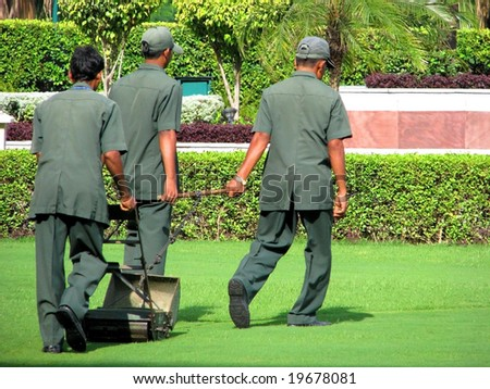 NEW DELHI - SEPT 8: On September 8, 2007 in New Delhi, India three men going green with a push / pull manual mower to avoid carbon emissions.