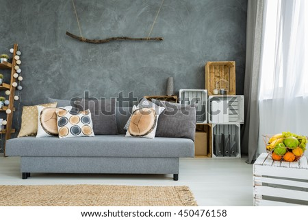 New design grey interior with sofa, DIY furniture and decorative stucco italiano wall